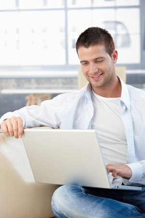 stubbly: Casual young man browsing internet at home, sitting on sofa, smiling. Stock Photo