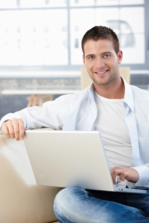 Handsome young man sitting on sofa at home, using laptop. Stock Photo - 8747277