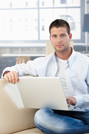 Goodlooking young man working at home, sitting on sofa, using laptop. Stock Photo - 8747324