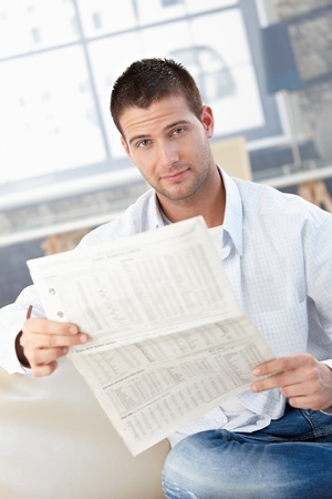 Handsome young man reading newspaper at home, sitting on sofa. Stock Photo - 8747306