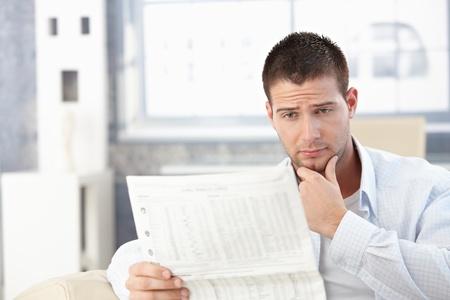 sadly: Giovane uomo lettura giornale a casa, cercando preoccupato.