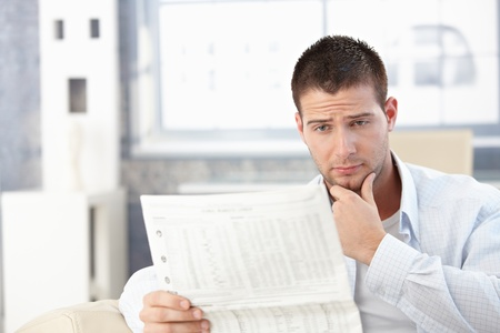 Young man reading newspaper at home, looking worried.