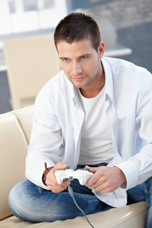 Handsome young man playing video game at home, sitting on sofa. Stock Photo - 8747328