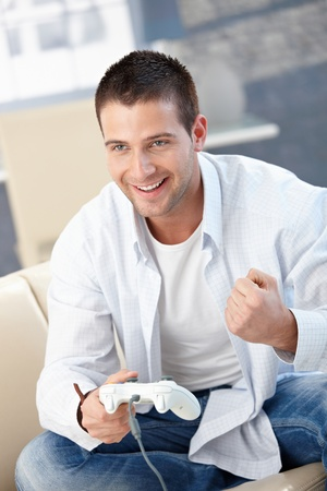 Goodlooking young man enjoying video game, sitting on sofa, playing, laughing. photo