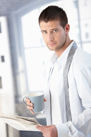 dressing up: Handsome young man getting ready in the morning, reading news, drinking tea.