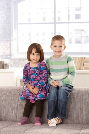 3 4 length: Smiling children sitting on sofa together, looking at camera. Stock Photo