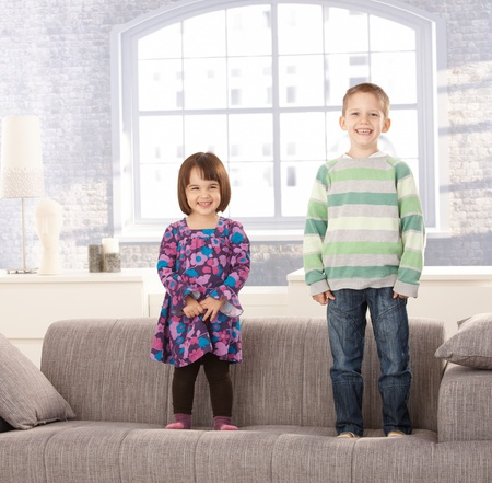age 5: Laughing kids standing on couch at home. Stock Photo