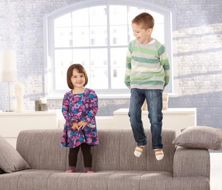 trois enfants: Enfants jouant sur le canap�, little boy de saut, petite fille debout, en riant.