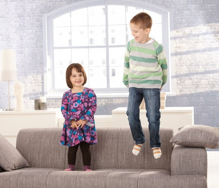 living room sofa: Kids playing on sofa, little boy jumping, small girl standing, laughing.