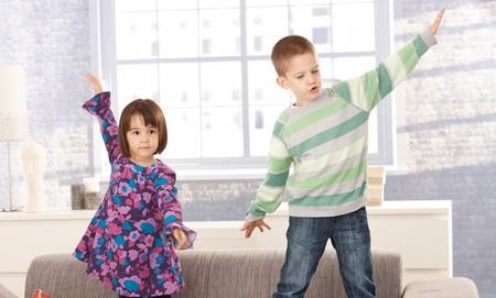 arms wide: Bambini che giocano sul divano insieme, con le braccia ampia aprire.