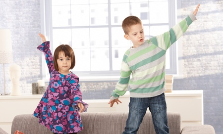 Children playing on sofa together, with arms wide open. photo