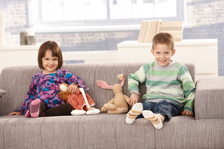 Happy kids sitting on sofa with toys, laughing at camera. photo