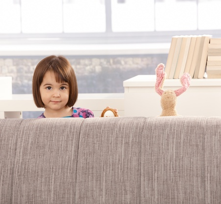 only 3 people: Portrait of cute little girl and toys half hiding behind sofa.