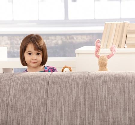 2 to 3 years: Ritratto di cute little girl e giocattoli mezza nascondersi dietro un divano. Archivio Fotografico