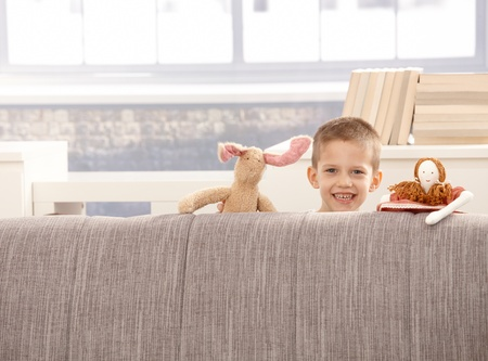 Cute little boy playing with toys at sofa, smiling at camera. photo