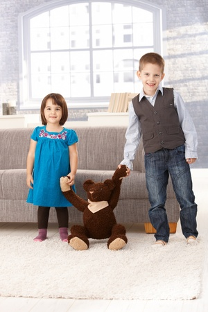 3 4 length: Little sister and brother standing at home holding hands with teddy bear, smiling.