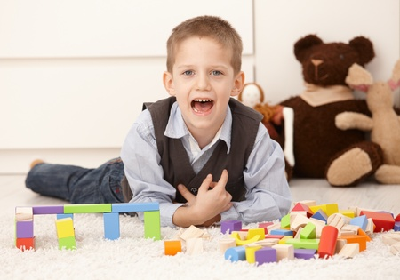 age 5: Cute kid playing at home, posing with mouth open, looking at camera. Stock Photo