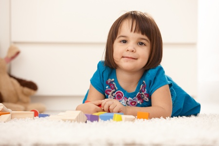 Portrait of cute little girl playing on floor, smiling at camera. photo