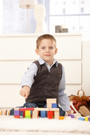 Cute kid proud, pointing at structure of building toys, smiling at camera. photo