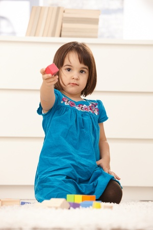 Small cute girl offering building block, playing on floor, looking at camera. photo