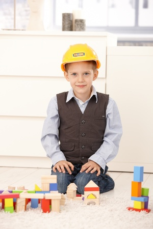 Portrait of smiling young boy kneeling in builder hat playing with building block set. photo