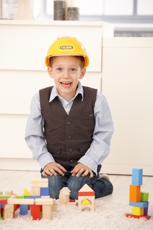 Happy small boy in hardhat with building block set, laughing at camera. Stock Photo - 8747444