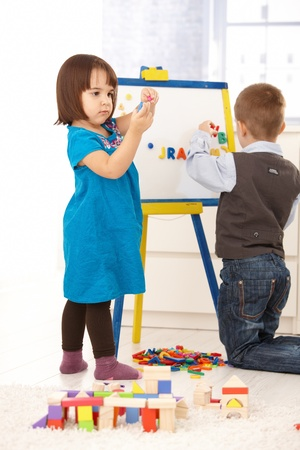 3 4 length: Children playing with magnetic drawing board and alphabet. Stock Photo