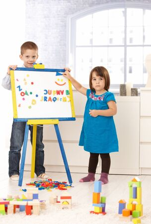 Portrait of creative small kids standing at drawing board, playing with alphabet.