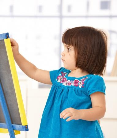 jouet: Jolie petite fille jouant avec la planche � dessin, se concentrant.