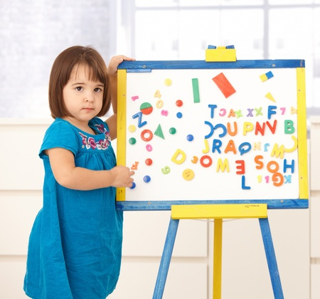 lost child: Cute little girl standing at drawing board, holding it, looking worried. Stock Photo