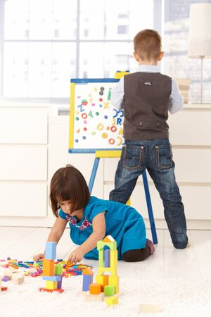 3 4 length: Little boy and girl playing together at home with drawing board and toy blocks.