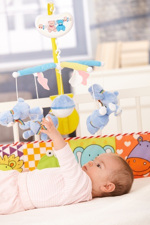 Baby girl lying in bed playing with colorful toys. Stock Photo - 8747429
