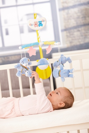 Baby playing with bed mobile toy, reaching up to teddy bear. Stock Photo - 8747401