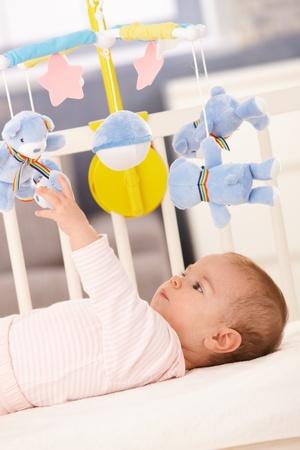 bebe cuna: Ni�a jugando en la cama con el oso de m�viles de juguete.