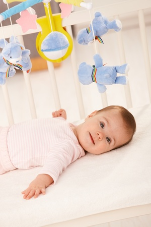 Portrait of baby girl in infant bed with toy bear. photo