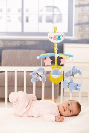 bebe cuna: Lindo beb� ni�a acostado en el pesebre con m�vil de juguete. Foto de archivo