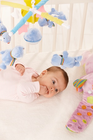 Small baby girl surrounded with colorful toys, with hand in mouth. photo