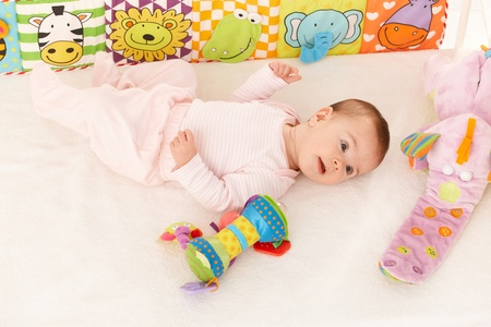 Infant girl lying on back surrounded with colorful baby toys photo