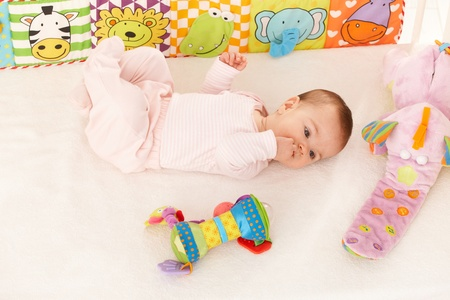Baby girl looking at colorful toy in bed, with hand in mouth. photo