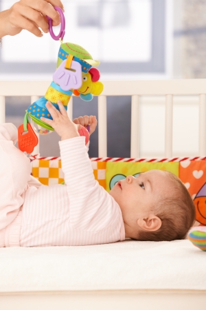 baby toy: Baby girl playing, mother holding infant toy to reach.