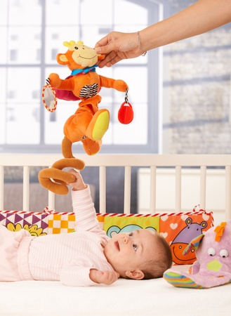 Happy baby girl playing in bed, mum holding colorful toy. photo