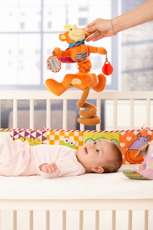 Cute infant girl playing with colorful toys, mother holding toy for baby. photo