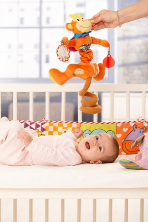Happy baby laughing in bed, mother holding colorful development toy. photo