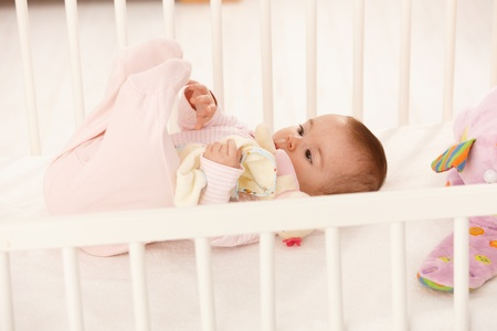 baby girl playing: Cute baby playing with feet in baby crib, holding toy. Stock Photo