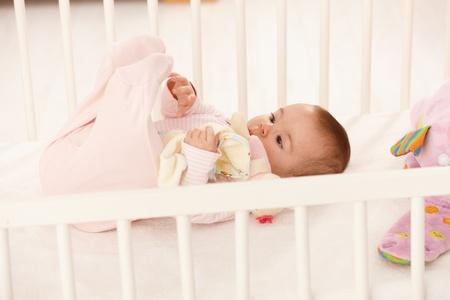 pie bebe: Lindo beb� jugando con los pies en la cuna del bebe, celebraci�n de juguete.