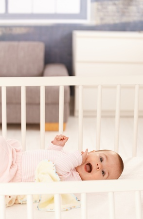 Cute baby girl wearing pink lying in white crib. photo