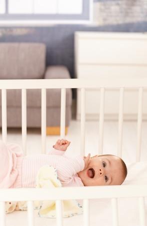 Cute baby girl wearing pink lying in white crib. photo