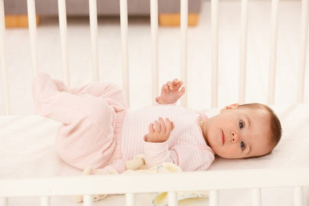 baby girl playing: Beautiful infant girl in cute pink dress lying in crib.