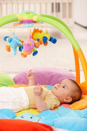 Baby girl lying on playmat, looking at toys. Stock Photo - 8747421