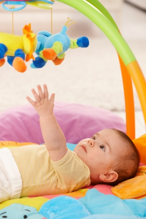 Baby reaching for colorful toy on playmat. photo